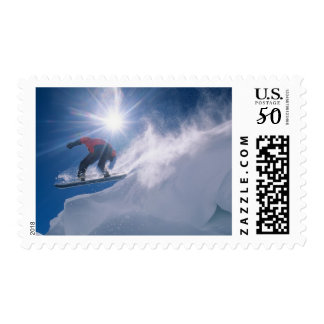 Man jumping off a large cornince on a snowboard postage