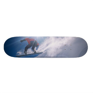 Man jumping off a large cornince on a snowboard skate board decks