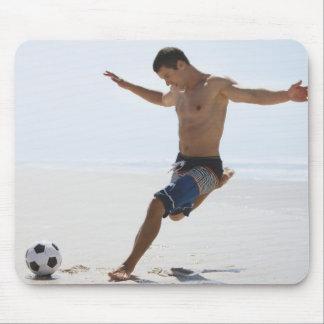 Man kicking soccer ball on beach mouse pad