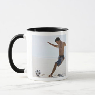 Man kicking soccer ball on beach mug