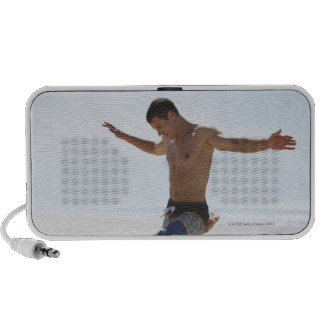 Man kicking soccer ball on beach notebook speakers
