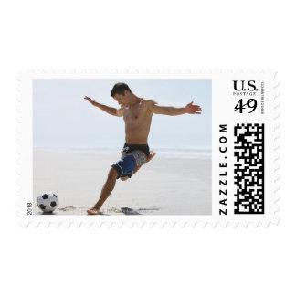 Man kicking soccer ball on beach postage