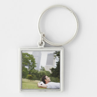 Man laying in urban park with soccer ball key chain