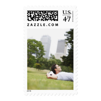 Man laying in urban park with soccer ball postage