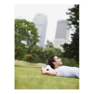 Man laying in urban park with soccer ball postcard
