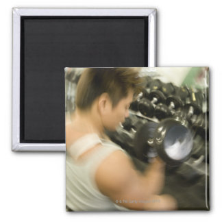 Man lifting dumbbell in gym, high angle view, 2 inch square magnet