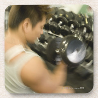 Man lifting dumbbell in gym, high angle view, coaster