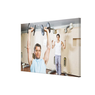 Man lifting weights at gym stretched canvas print