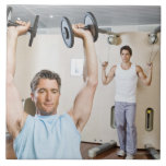 Man lifting weights at gym ceramic tile