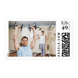 Man lifting weights at gym postage stamp