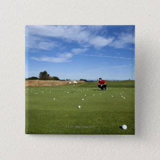Man lining up a putt while golfing. pinback button