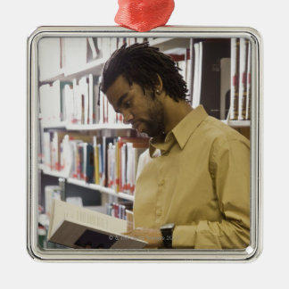 Man looking at book in library metal ornament