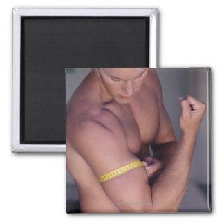 Man measuring bicep 2 inch square magnet