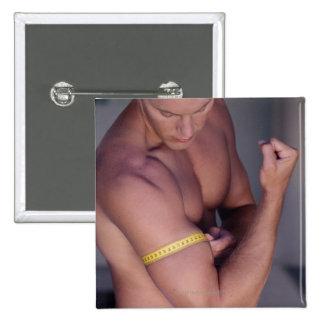 Man measuring bicep buttons