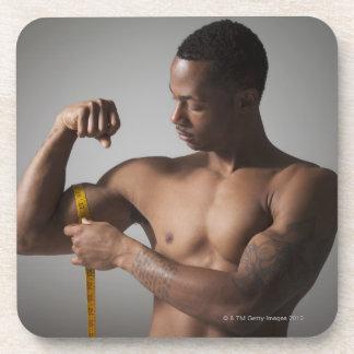 Man measuring his triceps beverage coaster