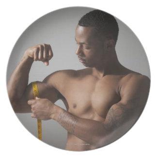 Man measuring his triceps melamine plate