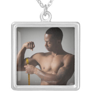 Man measuring his triceps silver plated necklace