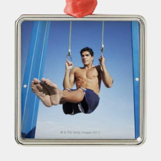 Man on a beach working out on exercise rings metal ornament
