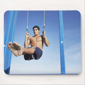 Man on a beach working out on exercise rings mouse pad