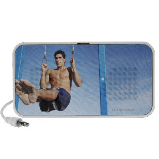 Man on a beach working out on exercise rings mp3 speaker