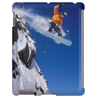 Man on a snowboard jumping off a cornice at