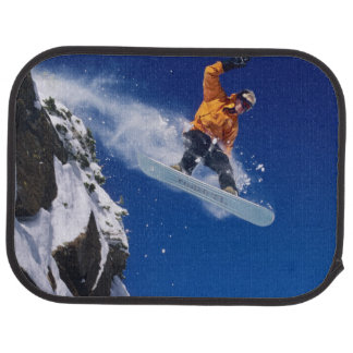 Man on a snowboard jumping off a cornice at car floor mat