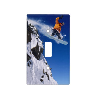 Man on a snowboard jumping off a cornice at light switch cover