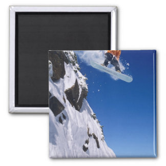 Man on a snowboard jumping off a cornice at magnet