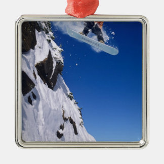 Man on a snowboard jumping off a cornice at metal ornament