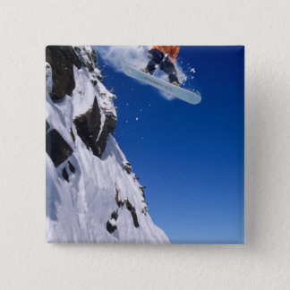 Man on a snowboard jumping off a cornice at pinback button