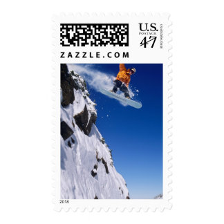 Man on a snowboard jumping off a cornice at postage