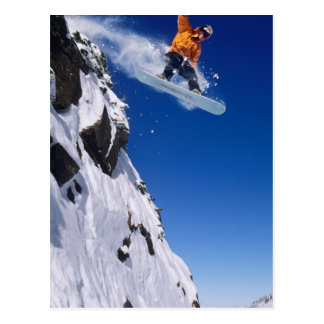 Man on a snowboard jumping off a cornice at postcard