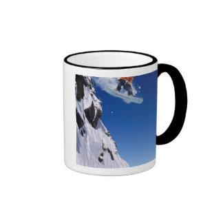 Man on a snowboard jumping off a cornice at ringer mug