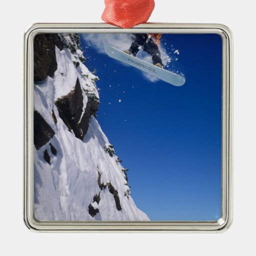 Man on a snowboard jumping off a cornice at square metal christmas ornament