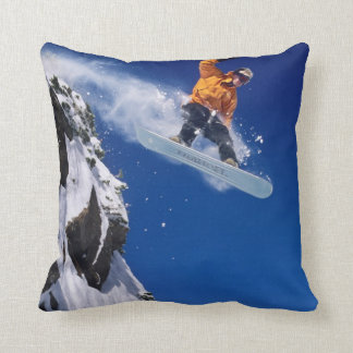 Man on a snowboard jumping off a cornice at throw pillow