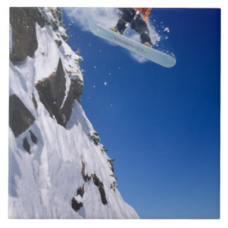 Man on a snowboard jumping off a cornice at tile