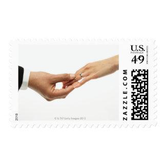 Man placing wedding band on woman's hand (focus postage