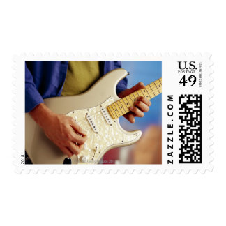 Man playing electric guitar postage