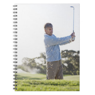 Man playing golf in sand trap notebook