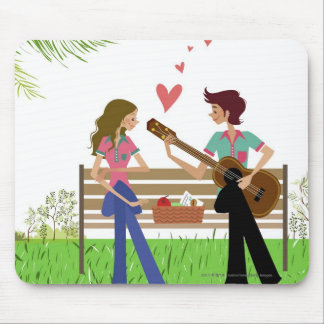 Man playing the guitar with a woman beside her mouse pad