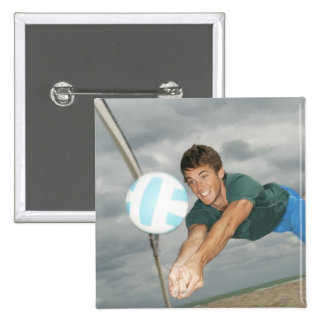 Man playing volleyball on the beach 2 inch square button