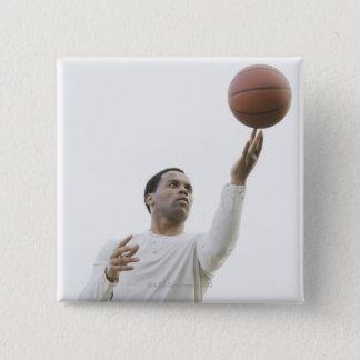 Man playing with basketball, studio shot pinback button
