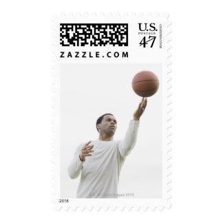 Man playing with basketball, studio shot postage stamp
