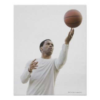 Man playing with basketball, studio shot poster