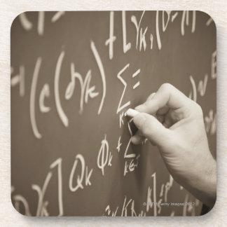 Man printing math equations on a chalkboard beverage coaster