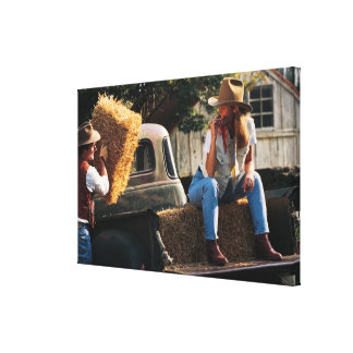 Man putting hay bales in truck with woman canvas print