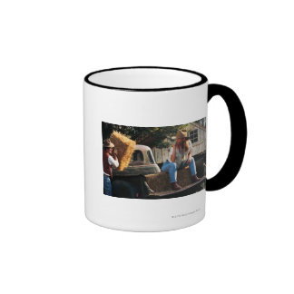 Man putting hay bales in truck with woman ringer mug