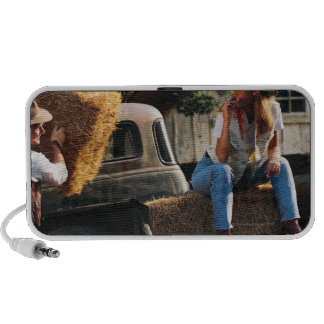 Man putting hay bales in truck with woman speakers