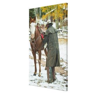 Man putting saddle on horse canvas print