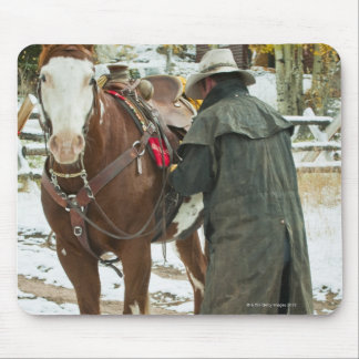 Man putting saddle on horse mouse pad